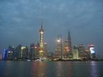 Город Шанхай - вечером город сверкает миллионами огней